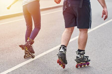 happy couple riding on roller skates holding hands in city