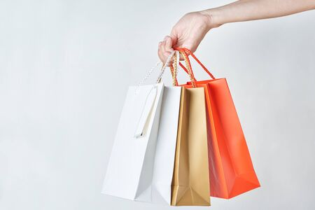 woman hand hold colorful paper shopping bags on white background, close up