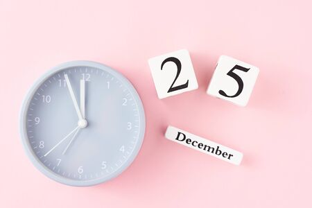 Christmas background with alarm clock and calendar wuth 25 december date on pastel pink background, top view. Flat lay minimalism style decorations