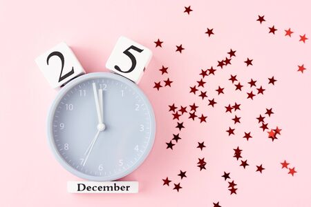 Christmas background with alarm clock and festive stars cofetti on pastel pink background, top view. Flat lay minimalism style decorations