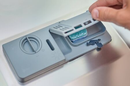 Hand putting soap tablet in dishwasher machine, close up. Kitchen domestic appliance concept