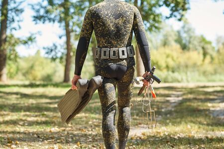 diver in wet suit and flippers with harpoon shotgun get ready for water hunting fishing