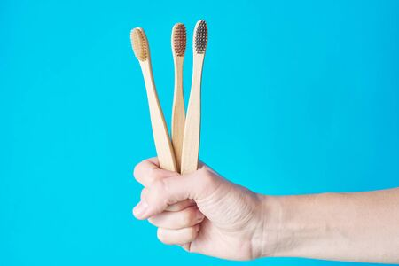 Three wooden eco friendly bamboo toothbrushes on blue background. Dental care conept