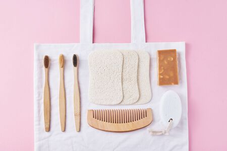 Body care natural wooden eco friendly products on pink background, flat lay top view. Bamboo toothbrushes, wooden comb, soap, spongle and natural washclothers. Zero waste concept