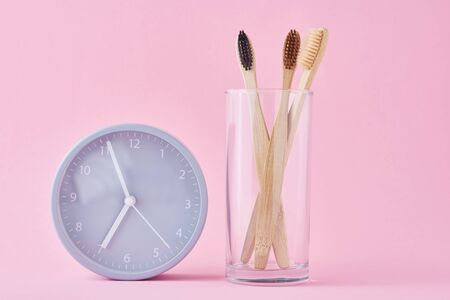 Three wooden bamboo toothbrushes in glass and alarm clock on pink background. Morning hygiene, dental care concept Stock Photo