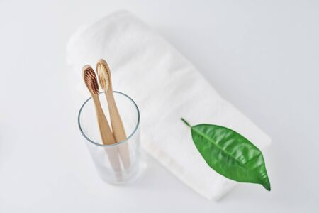 Two wooden bamboo eco friendly toothbrushes in glass and towel on white background.  Dental care and zero waste concept