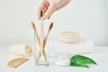 Woman hand take wooden bamboo toothbrush in bathroom interior. No plastic zero waste concept. Eco friendly toothbrushes in glass, towel, tooth powder and washcloth on white background