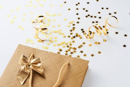 Christmas shopping and birthday congratulation concept. Golden shopping bag with festive glitter confetti on white background