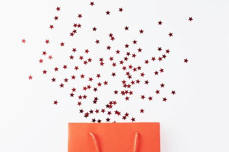 Shopping and birthday congratulation concept. Red shopping bag with festive glitter confetti on white background