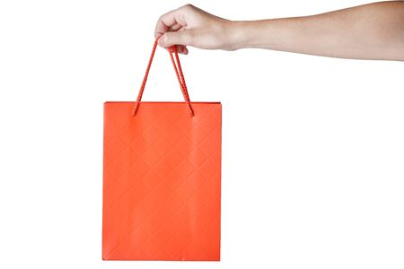 Woman hand hold red empty blank craft paper shopping bag isolated on a white background. Packaging template mockup