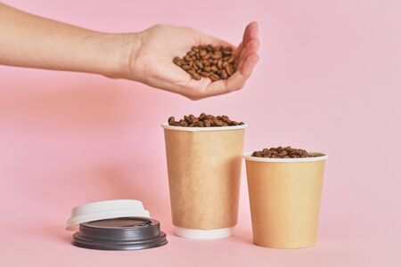 Female hand sprinkles coffee beans in coffee paper cup on a pink background