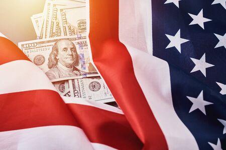 Bandera nacional de Estados Unidos y billetes de dinero en dólares estadounidenses. Concepto de negocios y finanzas