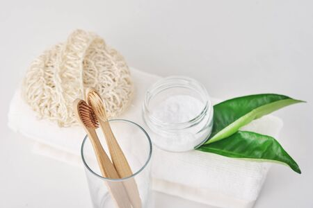 Wooden bamboo toothbrushes in glass, baking soda and towel on white background. Personal hygiene concept