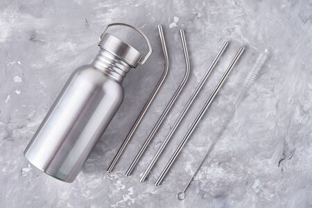 Reusable plastic free items on gray background. Top view of aluminun bottle and metal tubes. Zero waste eco friendly concept