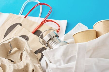 Zero waste concept. Eco friendly reusable items in natural shopping bag. Paper bag, coffee cups and metal bottle on blue background