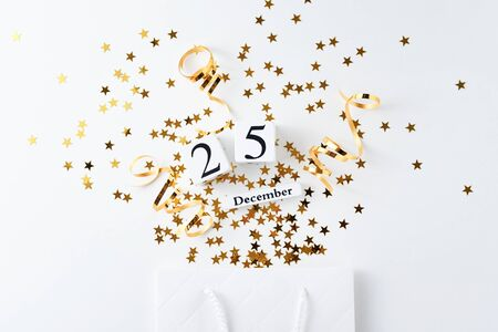 Christmas shopping concept. Shopping bag with festive glitter confetti and calendar with date 25 december on white background