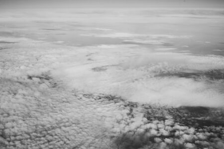 White fluffy clouds top view from airplane window. Black and white photo Reklamní fotografie