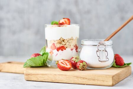 granola or yogurt with strawberry in glass, fresh berries and jar with sugar on cutting board