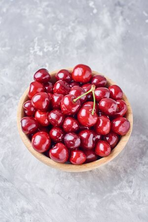 Red fresh cherry beries in wooden bowl on gray background, top view