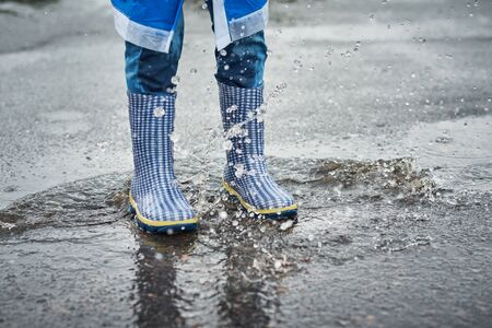 child in blue rubber boots jumping over puddle in the rain