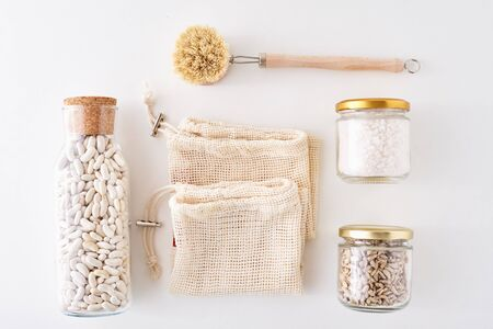 Glass jars with food ingredients on white background, top view. Zero waste concept. Kitchen background with eco friendly urensils