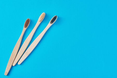 three wooden bamboo toothbrushes on blue background, top view.  Dental care concept