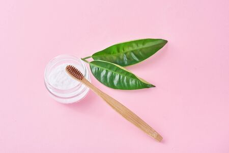 Wooden bamboo toothbrush with baking soda powder in glass jar and green leaves on pink background.  Teeth health and keep mouth concept