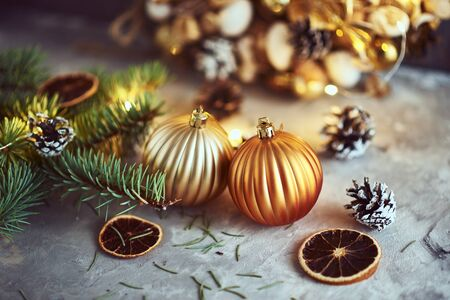 Christmas decorations with golden balls, fir tree branch and garland lights on dark background