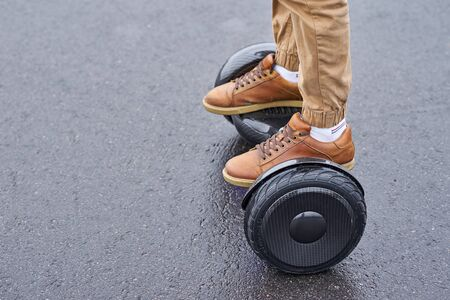Man using hoverboard on asphalt road, close up. Feet on electrical scooter outdoor