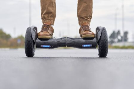 Man using hoverboard on asphalt road, close up. Feet on electrical scooter outdoor, front view 免版税图像