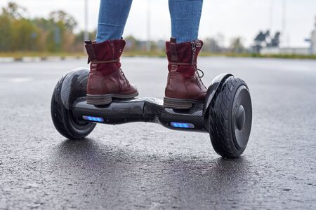 Woman using hoverboard on asphalt road, close up. Feet on electrical scooter outdoor
