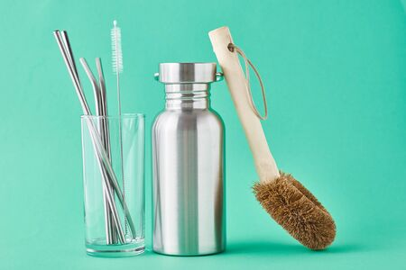 Zero waste concept. Eco friendly reusable items aluminun bottle and metal tubes in glass on green background