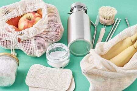 Reusable plastic free items on green background. Glass jar, metal straws, aluminum bottle, wooden cleaning brush and fruits in shopping bag, top view