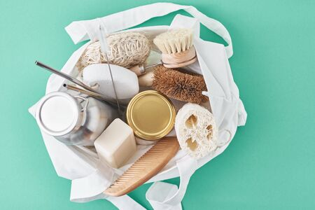 Reusable plastic free items in cotton shopping bag. Glass jar, metal straws, aluminum bottle and wooden cleaning brush on green background Reklamní fotografie