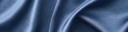 Silver silk background with folds.  Abstract texture of rippled silk surface, wide long banner