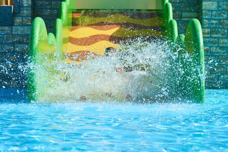 Woman and two boys on water park slides. Happy family ride on water slides with flowing splash in aqua park