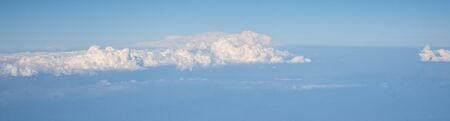 Aerial view of fluffy clouds. Top view of beautiful cloudscape and blue sky, long banner