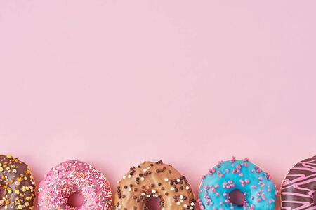 Different types of colorful donats decorated sprinkles and icing on pastel pink background with copy space