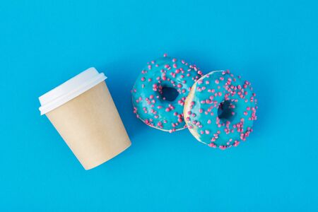 Cup of coffee and donuts on blue background, top view