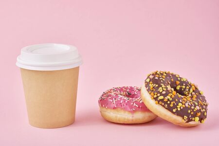 Cup of coffee and donuts on pink background