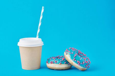 Cup of coffee and donuts on blue background Stock fotó