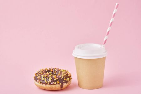 Cup of coffee and donut on pink background