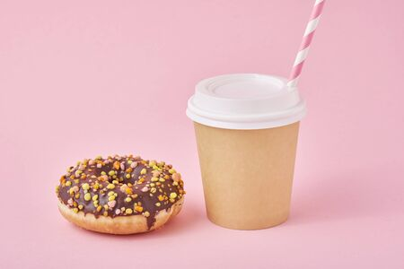 Cup of coffee take away and donut on pink background