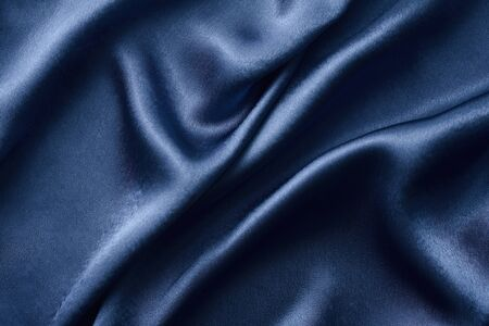 Silver silk background with folds.  Abstract texture of rippled silk surface