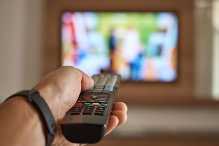 Man watching TV in the room and switches channels using remote control in his hand