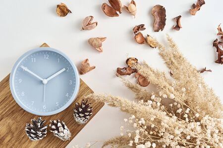 Alarm clock with decorations on white background, top view. Minimal flat lay style Stock Photo