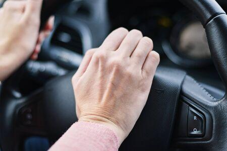 Mano del conductor presionó el botón de la bocina en la rueda del coche