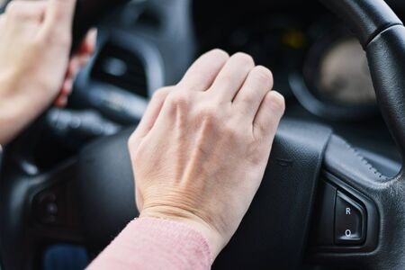 Pulsante clacson premuto a mano dal conducente sulla ruota dell'auto