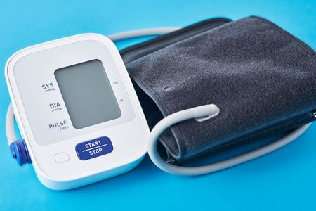 Digital blood pressure monitor on blue background, closeup. Helathcare and medical concept