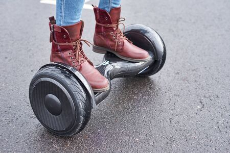 Woman using hoverboard on asphalt road, close up. Feet on electrical scooter outdoor Imagens